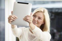 Mujer joven que usa la tablilla digital Imagen de archivo libre de regalías