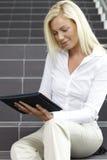 Mujer joven que usa la tablilla digital Imágenes de archivo libres de regalías