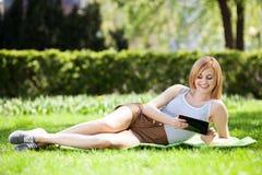 Mujer joven que usa la tablilla digital al aire libre Fotos de archivo