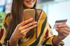 Mujer joven que usa la tarjeta elegante del teléfono y de crédito fotografía de archivo