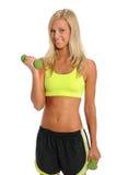 Mujer joven que usa pesas de gimnasia Imágenes de archivo libres de regalías
