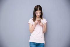 Mujer joven que usa smartphone Foto de archivo