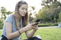 Mujer joven que usa smartphone en el parque foto de archivo