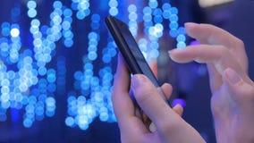 Mujer joven que usa smartphone en la exposición moderna de la tecnología almacen de video