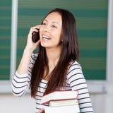 Mujer joven que usa smartphone en la universidad Imagen de archivo