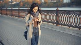 Mujer joven que usa smartphone Lectura de la muchacha en el teléfono celular, usando el app, comunicando en los medios sociales,  almacen de metraje de vídeo
