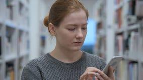 Mujer joven que usa Smartphone para en línea hojear almacen de video