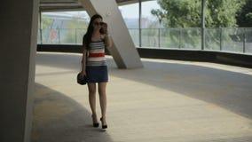 Mujer joven que usa smartphone y caminando en parque en ciudad almacen de metraje de vídeo