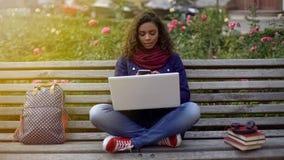 Mujer joven que usa smartphone y el ordenador portátil al aire libre, tiempo libre en banco en parque Imagen de archivo libre de regalías