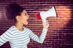 Mujer joven que usa su megáfono en la luz Foto de archivo libre de regalías