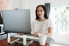 Mujer joven que usa su ordenador port?til en casa fotografía de archivo libre de regalías