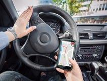 Mujer joven que usa su smartphone como GPS Imagen de archivo libre de regalías
