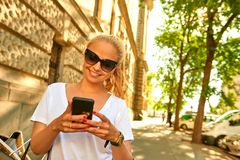 Mujer joven que usa su teléfono en la calle con los bolsos Foto de archivo