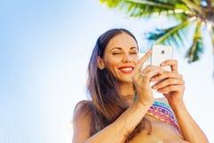 Mujer joven que usa su teléfono en la playa Imágenes de archivo libres de regalías