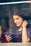 Mujer joven que usa tecnología en café Foto de archivo