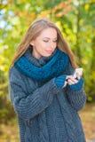 Mujer joven que usa un móvil al aire libre en otoño imagen de archivo libre de regalías