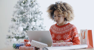 Mujer joven que usa un ordenador portátil en la Navidad Fotografía de archivo