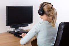 Mujer joven que usa un ordenador y una música que escucha Fotografía de archivo