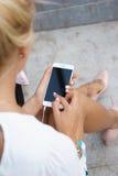Mujer joven que usa un smartphone Foto de archivo libre de regalías
