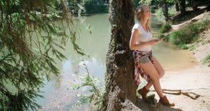 Mujer joven que usa un smartphone en un bosque Fotos de archivo libres de regalías