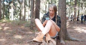 Mujer joven que usa un smartphone en un bosque Imagen de archivo libre de regalías