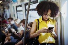 Mujer joven que usa un smartphone en el subterráneo Foto de archivo