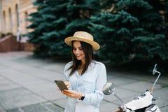Mujer joven que usa un smartphone mientras que hace una pausa su moto Foto de archivo