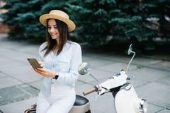 Mujer joven que usa un smartphone mientras que hace una pausa su moto Fotos de archivo