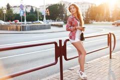 Mujer joven que usa un smartphone mientras que hace una pausa la cerca Imagen de archivo libre de regalías