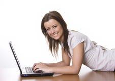 Mujer joven que usa una computadora portátil Imagenes de archivo