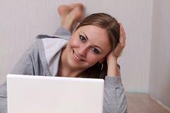 Mujer joven que usa una computadora portátil Fotos de archivo