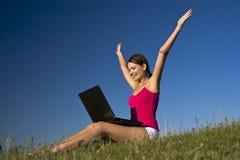 Mujer joven que usa una computadora portátil, y feliz hermosos. Fotografía de archivo