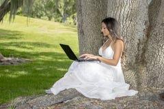 Mujer joven que usa una computadora portátil Foto de archivo