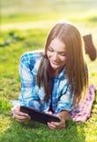 Mujer joven que usa una tableta al aire libre Imagenes de archivo