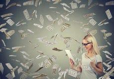 Mujer joven que usa una tableta que construye el dinero en línea de la ganancia de negocio debajo del efectivo que cae abajo foto de archivo libre de regalías