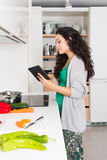 Mujer joven que usa una tableta para cocinar Imágenes de archivo libres de regalías
