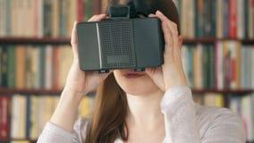Mujer joven que usa VR 360 vidrios en casa Considerando algo la excitación, haciendo gesticula con las manos almacen de video