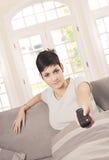 Mujer joven que ve la TV Fotos de archivo