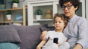 Mujer joven que ve la TV con el muchacho lindo que lo frota ligeramente y que besa que expresa amor almacen de video