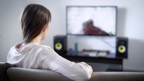 Mujer joven que ve la TV el sentarse en el sofá en sala de estar, ella tiene interés en la película, género de la novela de suspe almacen de metraje de vídeo
