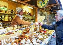 Mujer joven que vende cerámica y la miel en el mercado de la Navidad de Riga Imágenes de archivo libres de regalías