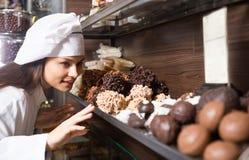 Mujer joven que vende los chocolates y la confitería finos en café imagen de archivo