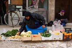 Mujer joven que vende verduras en un bazar de Damasco Imagen de archivo