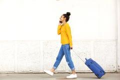 Mujer joven que viaja con la maleta y el teléfono móvil Imagen de archivo libre de regalías