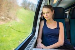 Mujer joven que viaja en tren imagen de archivo