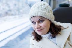 Mujer joven que viaja en tren y que mira hacia fuera la ventana Fotografía de archivo libre de regalías