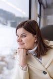 Mujer joven que viaja en tren y que mira hacia fuera la ventana Foto de archivo libre de regalías
