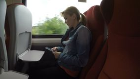 Mujer joven que viaja solamente en un tren cómodo al campo usando su smartphone - almacen de metraje de vídeo