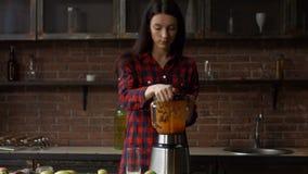 Mujer joven que vierte el smoothie sabroso en el vidrio metrajes