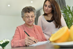 Mujer joven que visita a su abuela en una clínica de reposo fotografía de archivo